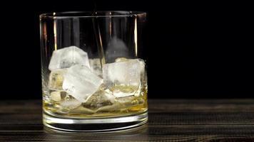 el whisky se vierte en un vaso con hielo