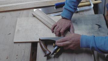un carpintero procesa una pieza en bruto de madera en ángulo con una cepilladora. un leñador viene con una cepilladora. 4k. Vídeo 4k. camara lenta. 24 fps video