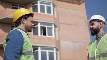 dois trabalhadores conversam sobre negócios em uma construção