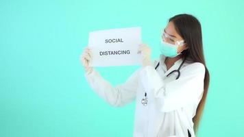 Mujer asiática médico mostrar cartel con texto distanciamiento social