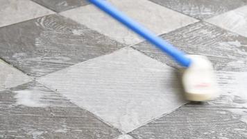 limpar o piso de ladrilho com uma escova de limpeza para pisos. video