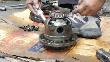 El técnico está utilizando las herramientas para desmontar los engranajes del eje de transmisión de los automóviles.