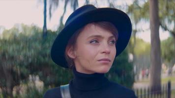 Cerca de una mujer con un sombrero mirando y sonriendo a la cámara