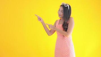 mujer asiática apunta hacia el lado izquierdo con espacio de copia