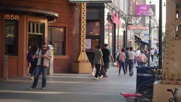 People Walking On Sidewalk Under Train Station