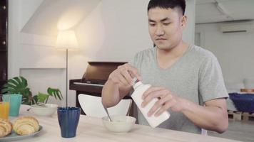 heureux homme asiatique prenant le petit déjeuner, céréales au lait, pain et boire du jus d'orange après le réveil le matin. video