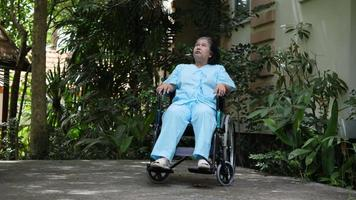 idosa com deficiência sentada em uma cadeira de rodas em um parque de hospital