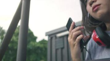 bela jovem asiática ouvindo música em um telefone inteligente na cidade. jovem mulher asiática relaxante ouvindo música na rua. video