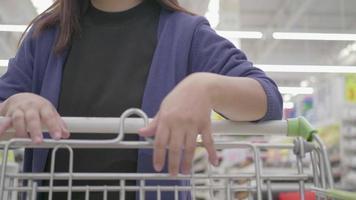 mulher asiática às compras com um carrinho de mercado.