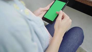 mujer con dispositivo de teléfono inteligente con pantalla verde.