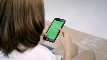 Joven mujer asiática con un teléfono inteligente con pantalla verde