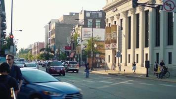pessoas andando nas faixas de pedestres nas ruas de Chicago com carros em primeiro plano