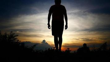 Silhouetten des Menschen gewinnen auf dem Hintergrund des Sonnenuntergangshimmels