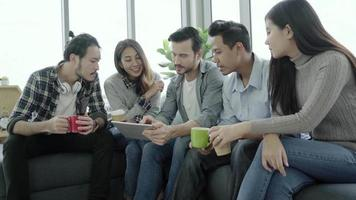 Multiethnic creative team diversity of young people group team holding coffee cups and discussing ideas meeting with tablet sitting on the couch at office.
