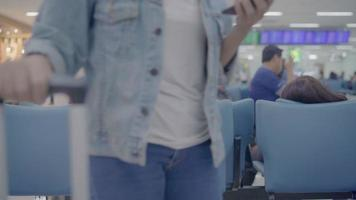 Happy Asian woman using and checking her smartphone while sitting on chair in terminal hall. video