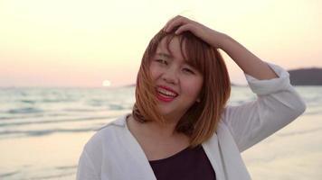 jovem asiática se sentindo feliz na praia