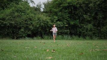 cámara lenta, niña feliz corriendo y sonriendo en el parque