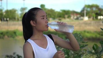 mujer joven bebiendo agua después del ejercicio