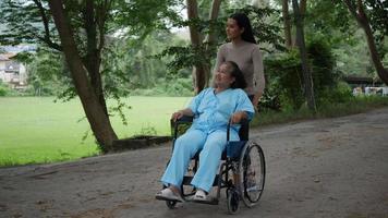 Mujer mayor con su hija empujando la silla de ruedas por el parque