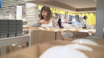 joven mujer asiática paseos carrito de compras eligiendo muebles nuevos en el almacén.