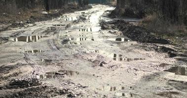 Camino sucio con muchos charcos de barro después de la lluvia