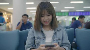 Happy Asian woman using and checking her smartphone while sitting on chair in terminal hall while waiting her flight at the departure gate in international airport. video