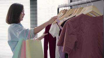 mulher asiática comprar roupas. comprador olhando para roupas no trilho dentro de casa na loja de roupas. lindo modelo de mulher asiática sorridente feliz. tiro médio. video
