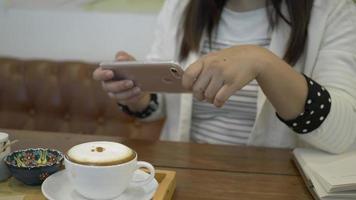 Frau macht ein Foto von ihrem Cappuccino mit einem Smartphone.