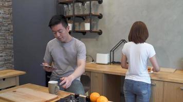 lindo casal asiático feliz está alimentando um ao outro na cozinha. homem usando o tablet e bebendo uma xícara de café. jovem casal asiático tem momentos românticos enquanto fica em casa.