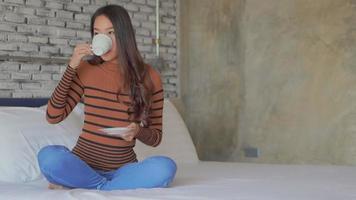 jovem mulher asiática tomando café na cama