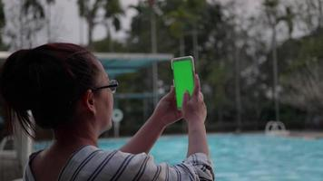 Woman taking picture with green screen in smart phone at resort swimming pool in the evening. video
