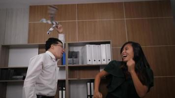 dois colegas alegres em ternos formais dançando alegres no escritório video
