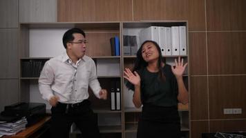 Dos colegas alegres en trajes formales bailando alegre en Office