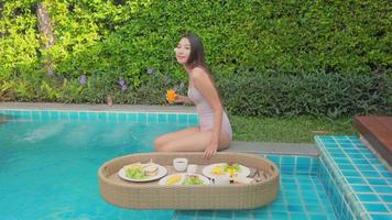 Young Asian woman enjoying a floating breakfast in the swimming pool