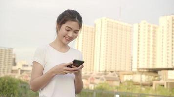 Frau, die Touchscreen-Technologie am Smartphone beim Gehen auf der Straße verwendet.