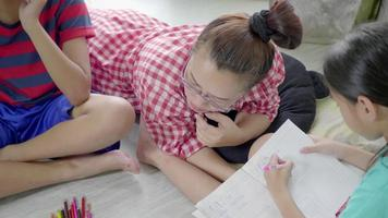 mère asiatique jouant avec des enfants au sol du salon.