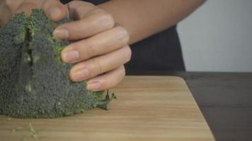 Slow motion - Close up of chief woman making salad healthy food and chopping broccoli on cutting board in the kitchen.