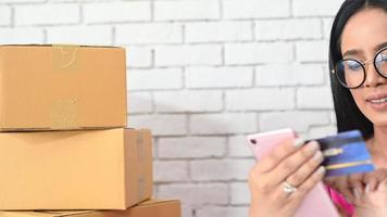 mujer escribiendo el número de una tarjeta de crédito en un teléfono video