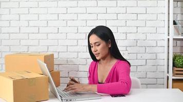 Mujer escribiendo el número de una tarjeta de crédito en un portátil. video