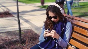 mujer joven escuchando musica en el parque