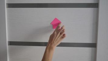 feche as mãos de uma mulher espetando papéis rosa