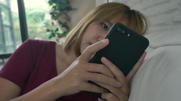 Asian woman playing smartphone while lying on home sofa in her living room. Happy female use phone for texting, reading, messaging and buying online at home. video