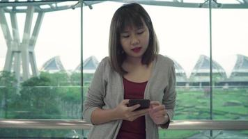 atraente casual feliz jovem asiática no aeroporto internacional. video