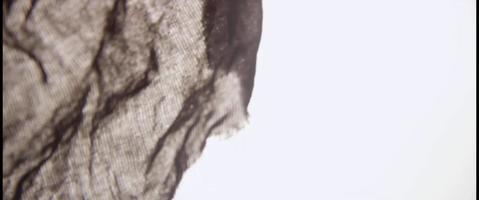 tecido escuro movendo-se como uma cauda de peixe em um líquido claro e um fundo claro em 4k