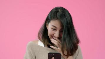Mujer asiática joven que usa el teléfono inteligente que controla las redes sociales sintiéndose feliz sonriendo en ropa casual.