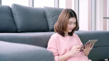 mulher asiática gravando um vídeo em seu tablet video