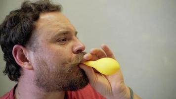 homem explodindo um balão amarelo