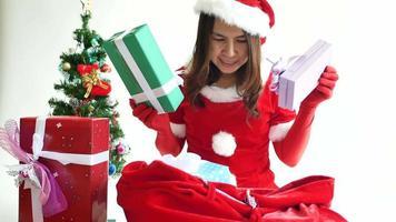 mujer vestida como la sra. claus preparando una bolsa de regalo para navidad