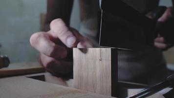 primer plano, carpintero, aserrar una tabla de madera con una sierra de mano