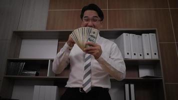 homme d & # 39; affaires disperse les dollars et danse drôle dans un bureau